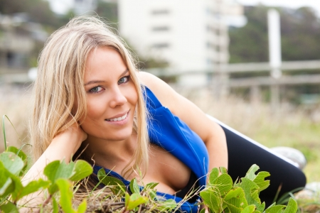 Close-up portrait of a woman lying in the grass. She is leaning on one elbow and smiling at the camera. Horizontal shot. photo
