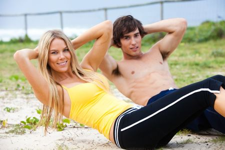 Portrait of a young couple smiling at the camera in the midst of doing sit-ups. The ocean can be seen in the background. Horizontal shot. Stock Photo