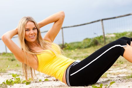 Portrait of a young woman smiling at the camera in the midst of doing sit-ups on a grassy beach. Horizontal shot. photo