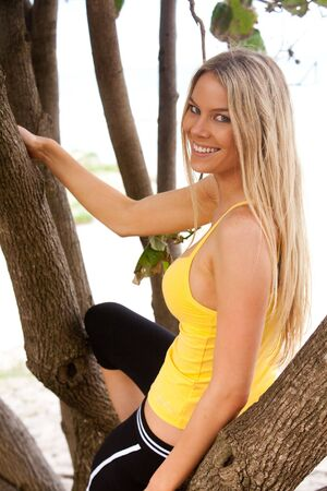 Portrait of a young woman sitting in a tree. She is smiling over her shoulder at the camera. Vertical shot. photo