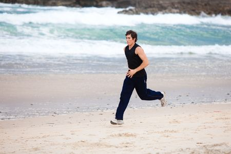 Full length profile view of a young man running in the surf on the beach. Horizontal shot. photo