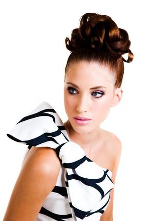 cabello negro: Retrato de una mujer joven. Su cabello con el estilo en un updo y ella es que llevaba un vestido blanco y negro con un gran arco en el hombro. Un disparo vertical. Aislados en blanco. Foto de archivo