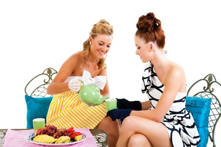 Portrait of two young women sitting at a table having tea. They are formally dressed and wearing gloves. Horizontal shot. Isolated on white. Stock Photo - 7003145