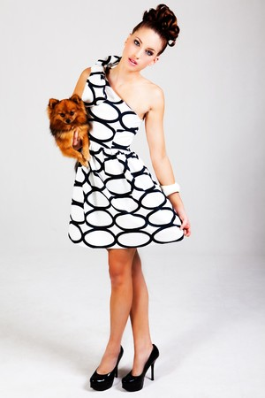 Portrait of a young woman holding a small dog. She is dressed in a black and white dress. Vertical shot. Stock Photo