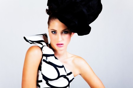 Portrait of a young woman. She is wearing a large hat and a black and white dress with a bow on the shoulder. Horizontal shot. Stock Photo - 7003116