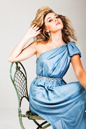 Portrait of a young woman with blonde hair wearing an elegant blue dress. She is sitting in a chair, leaning her head back and running her fingers through her hair. Vertical shot. Stock Photo - 7003171