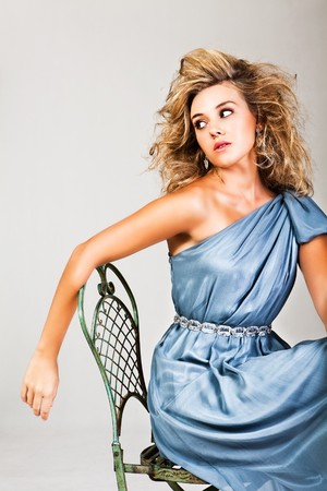 Portrait of a young woman with blonde hair wearing an elegant blue dress. She is sitting in a chair and looking behind her. Vertical shot.