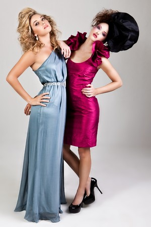 Two young women dressed in glamorous, avant garde attire. Vertical shot. photo