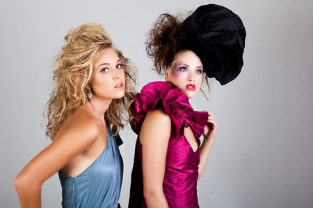 Two young women dressed in glamorous, avant garde attire. Horizontal shot. photo
