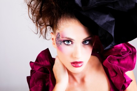 avant garde: High angle view of young woman dressed in avant garde attire. She is wearing a hat and has cosmetic artwork on her right temple. Horizontal shot.