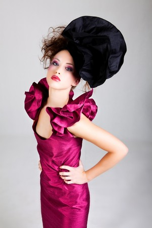 avant garde: High angle view of young woman dressed in avant garde attire. She is wearing a hat and has cosmetic artwork on her right temple. Vertical shot.