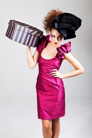 avant: A young woman dressed in avant garde attire and carrying a hat box. She is wearing a hat and has cosmetic artwork on her right temple. Vertical shot.
