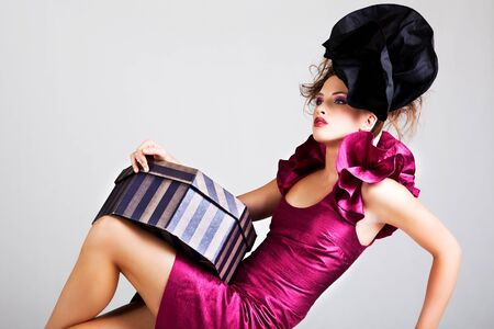 avant: A young woman dressed in avant garde attire and holding a hat box. She is wearing a hat and has cosmetic artwork on her right temple. Horizontal shot.