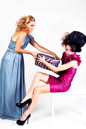 Two young women dressed in avant garde attire, fighting over a hat box. Vertical shot. photo