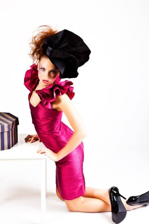 avant garde: A young woman dressed in avant garde attire and kneeling near a hat box. She is wearing a hat and has cosmetic artwork on her right temple. Horizontal shot. Stock Photo
