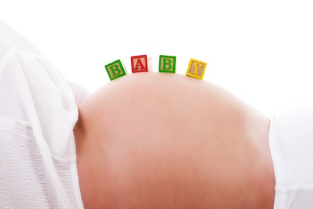 A set of baby blocks spelling out BABY are balanced on the stomach of a pregnant woman. Horizontal shot. Isolated on white. photo