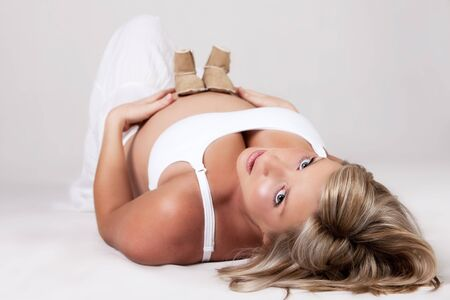 A young pregnant woman is lying on the floor on her back with booties on her stomach and looking at the camera. Horizontal shot. photo