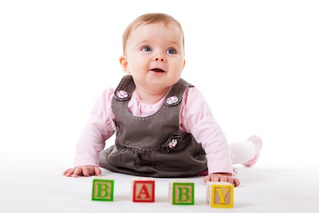 cute baby girl: A cute baby girl is posing behind a set of childrens blocks that spell out BABY.  Horizontal shot.