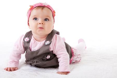 baby crawling: Una ni�a es rastrear a lo largo de la planta con una mirada inquisitiva en su cara.  Horizontal de disparo.