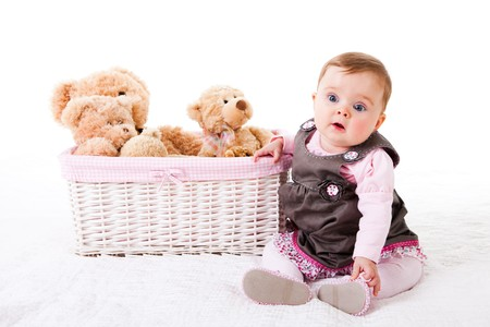 A cute baby girl is sitting on the floor next to a basket of teddy bears.  Horizontal shot.