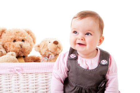 A baby girl is sitting next to a basket of teddy bears and smiling.  Horizontal shot. photo