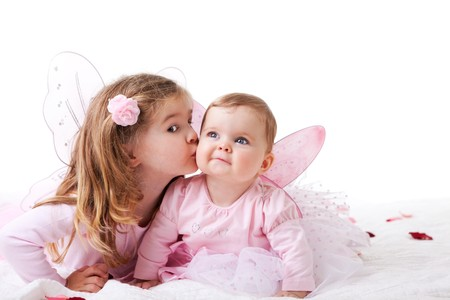 sibling: Two sisters are dressed up as fairies.  The older sister is kisssing the baby sister on the cheek.  Horizontal shot.