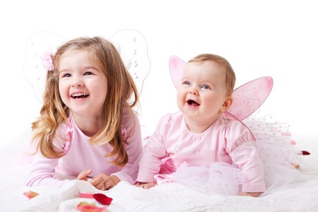 A baby girl and her older sister lie on the ground in fairy outfits.  Horizontal shot. Stock Photo