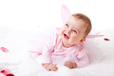 A cute baby girl in fairy wings laughs while lying on the ground covered in flower petals.  Vertical shot. Stock Photo