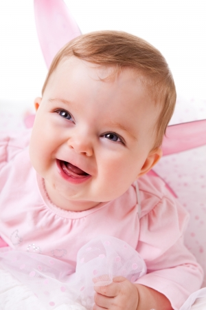 A cute baby girl in fairy wings laughs while looking up at the camera.  Vertical shot. Stock Photo