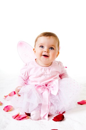 A cute baby girl dressed in a fairy costume sits amongst flower petals and smiles upwards.  Vertical shot.