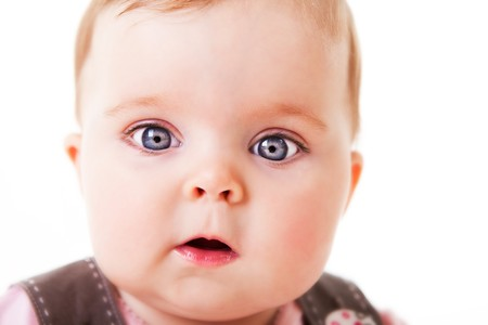 A cute baby girl looks in awe at the camera.  Horizontal shot.  Isolated on white.