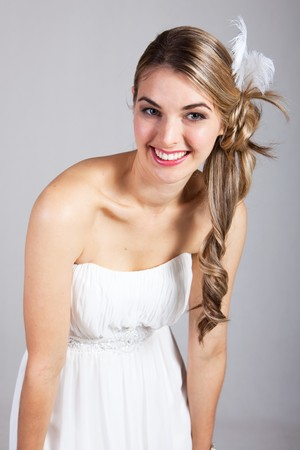 strapless dress: Attractive young woman wearing a white strapless dress and a feather hairpiece poses and smiles. Vertical shot.