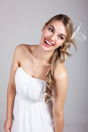 strapless dress: Attractive young woman wearing a white strapless dress and a feather hairpiece poses and laughs. Vertical shot.
