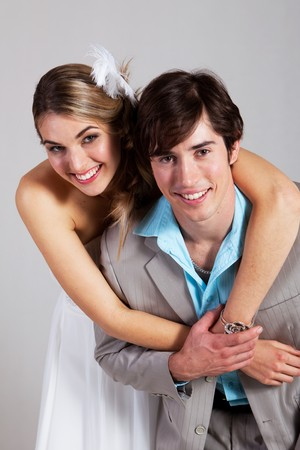 Young woman in a strapless dress has her arms around her boyfriend as the smile at the camera. Vertical shot. photo
