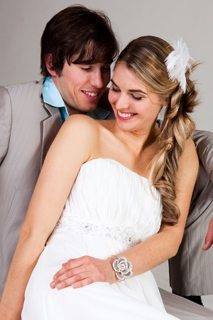 strapless dress: Attractive young couple sitting affectionately together. The man is wearing a suit and the woman is in a strapless dress. Vertical shot. Stock Photo