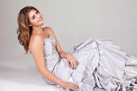 strapless dress: Beautiful young woman sits on the ground in a strapless dress and smiles at the camera. Horizontal shot. Stock Photo