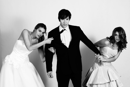 Two attractive young women wearing formal attire are pulling a young man in a suit between them. Horizontal shot. Stock Photo