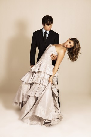 An attractive young couple in the midst of a dance move are dressed in formal attire. Vertical shot.