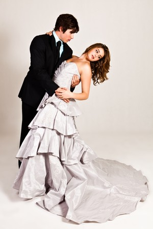 evening gown: An attractive young couple in the midst of a dance move are dressed in formal attire. Vertical shot.