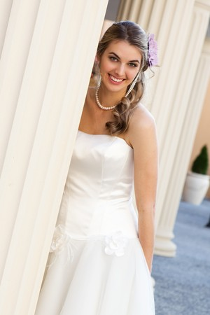 An attractive young woman wearing a white dress and pearls is smiling and standing behind a pillar. She has a purple flower in her hair.  Vertical shot.