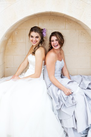 Two attractive young women wearing formal dresses are smiling and sitting back to back in an alcove. Vertical shot. Stock Photo