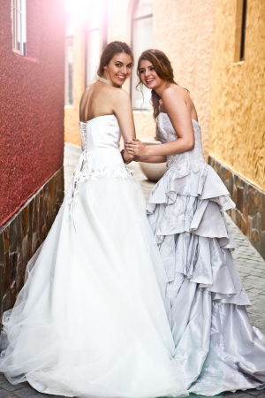 strapless dress: A young bride and her bridesmaid smile back at the camera while walking down an alley. Vertical shot. Stock Photo