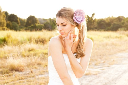 An attractive young woman wearing white wedding dress is standing in the middle of a dirt road in a rural landscape. She is wearing pearls and a purple flower in her hair. Horizontal shot. photo
