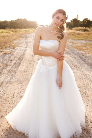 hairpiece: An attractive young bride wearing a white wedding dress is standing in the middle of a dirt road in a rural landscape while looking at the camera. Vertical shot.