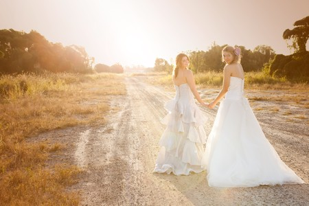 Attractive young bride and bridesmaid in formal attire looking over their shoulders at the camera.  They are walking on a country road. Horizontal shot.