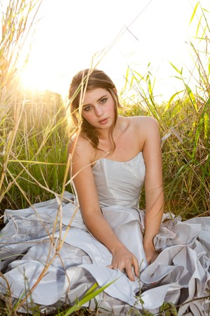 An attractive young woman wearing formal attire is sitting in a grass field. Vertical shot. photo