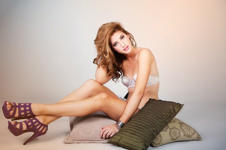 Attractive young woman wearing lingerie and high heels sits on a stack of pillows while looking into the camera. Horizontal shot.