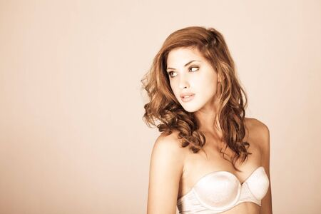 Attractive young woman with red hair models a strapless bra. Horizontal shot. photo