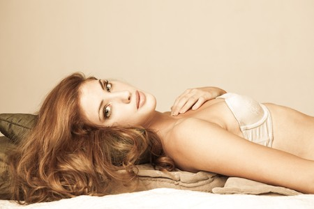Sensual young woman with long red hair lies atop pillows. She is wearing a strapless bra and looking into the camera. Horizontal shot. Stock Photo