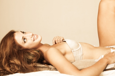 Sensual young woman with long red hair lies atop pillows. She is wearing a strapless bra and smiling upwards. Horizontal shot. Stock Photo